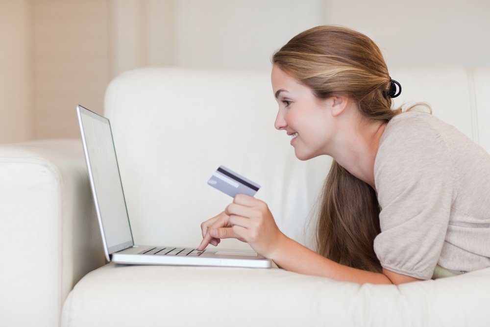 Side view of young woman on the sofa shopping online.jpeg